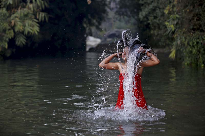A devotee takes a holy bath in River Saali in Sankhu during the Swasthani Brata Katha festival, a month-long festival where devotees recite one chapter of a Hindu tale daily from the 31-chapter sacred book, in Kathmandu, Nepal, on January 24, 2016. Photo: Reuters