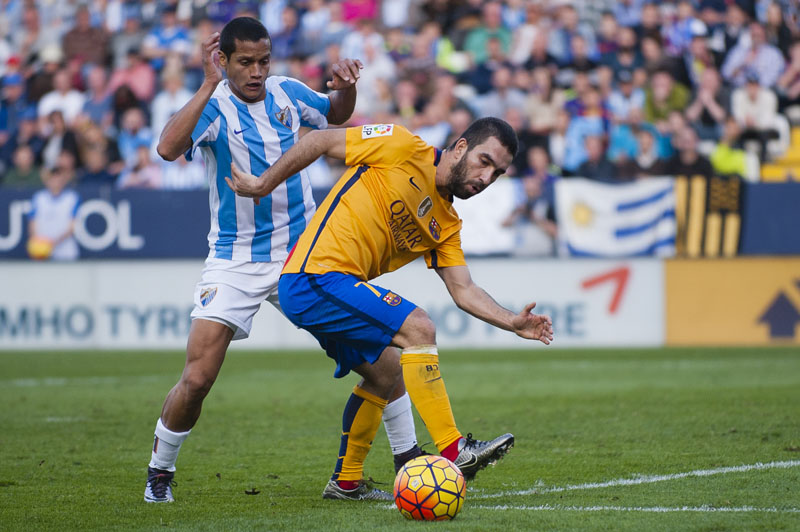 FC Barcelona's Arda Turan (right) duels for the ball against Malaga's Roberto Jose Rosales (left) during a Spanish La Liga soccer match between Malaga and Barcelona at La Rosaleda stadium in Malaga, Spain, on Saturday, January 23, 2016. Photo: AP