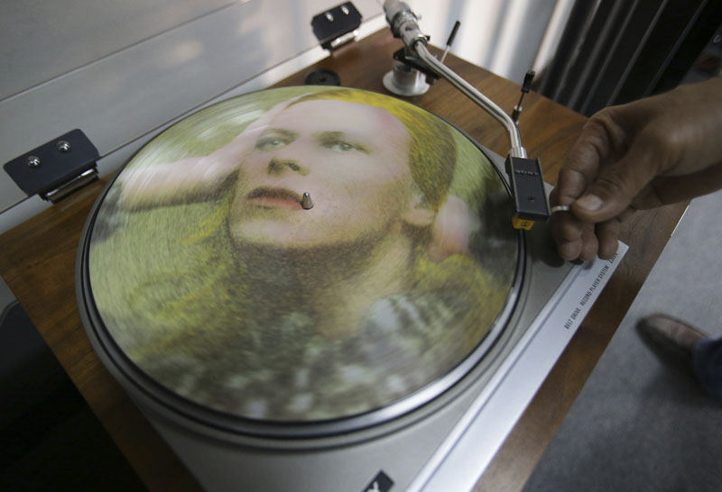 Rene Rivo, a Filipino David Bowie fan, plays a picture disc of Bowie's Hunky Dory on a turntable at his shop in suburban Paranaque, south of Manila, Philippines. Bowie, the chameleon-like star who transformed the sound - and the look - of rock with his audacious creativity and his sexually ambiguous makeup and costumes, died of cancer on Sunday, January 10. Photo: AP