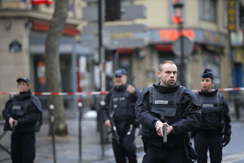 Police officers secure the perimeter near the scene of a fatal shooting which took place at a police station in Paris, Wednesday, January 7, 2016. Photo: AP