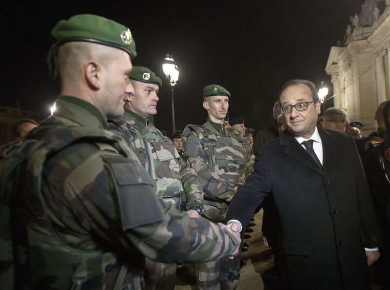 France's President Francois Hollande (right) shakes hands with a foreign legionnaire as he visits the security measures at the Champs Elysees in Paris on Thursday, December 31, 2015. Photo: AP