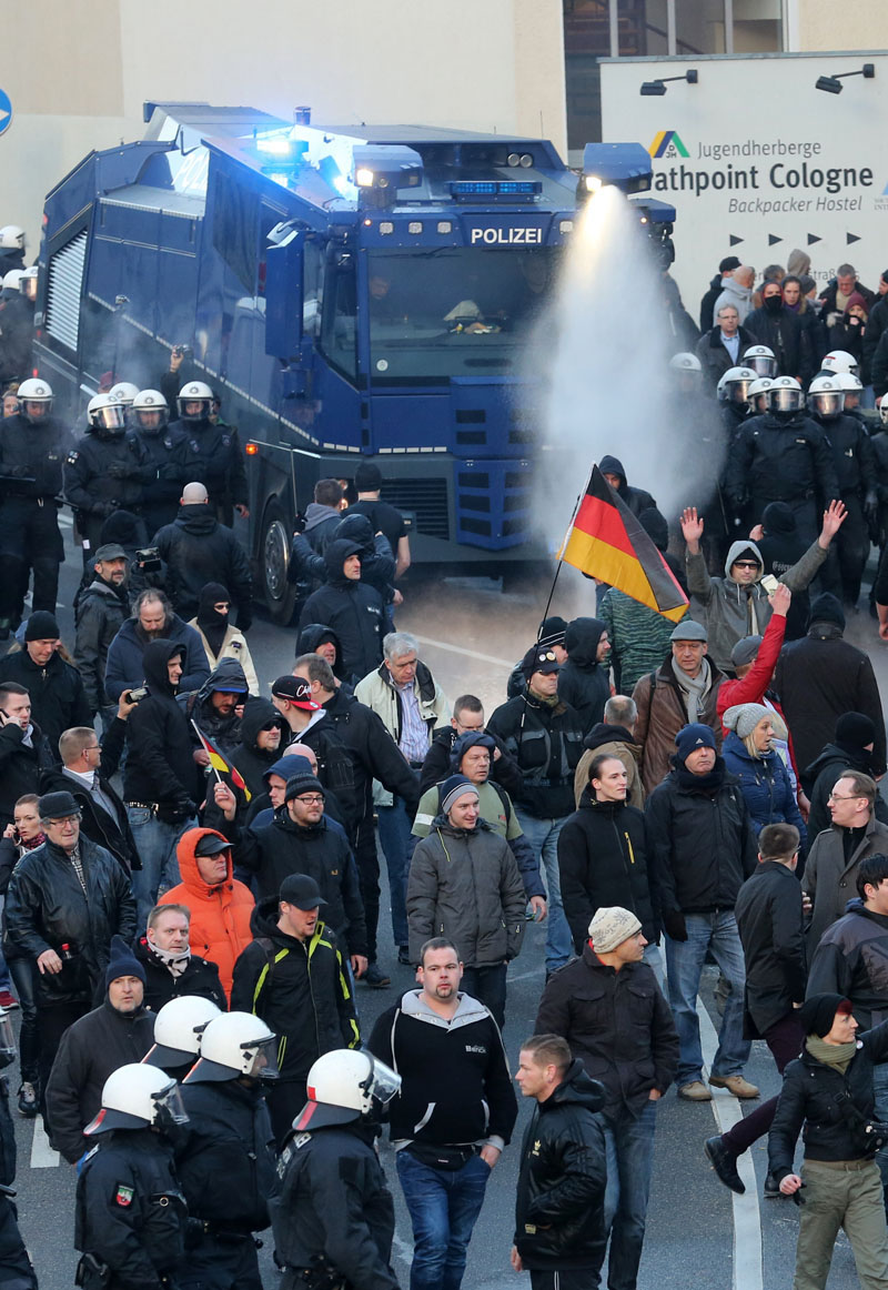 Police  drive back right-wing demonstrators using a water cannon during protests in Cologne, Germany, on Saturday January 9, 2016. Photo: via AP