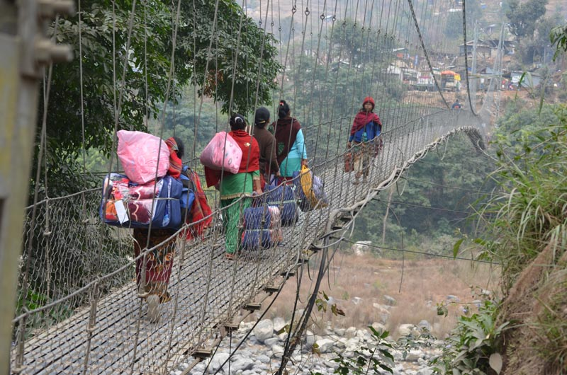 Chepang people, survivors of the last year earthquakes, return to their shelter crossing the Chumkhola stream in Makaising VDC of Gorkha district after they receive warm  clothes from Asal Chhimekee Nepal, a Pokhara-based NGO, on Thursday, January 28, 2016. Courtesy: Anita Dahal