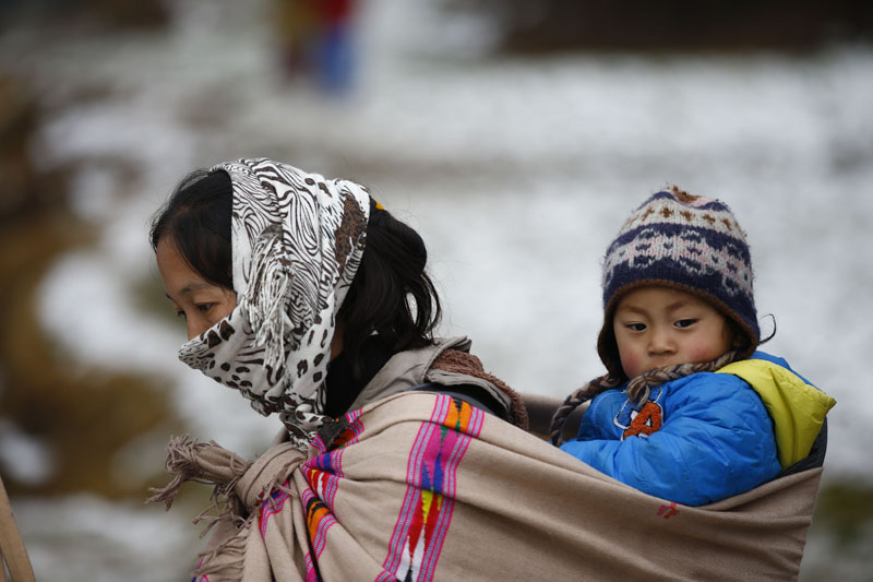 A mother with her child waits to receive winter relief materials in Helumbu, a village located in Sindhupalchok district, on Thursday, January 21, 2016. Photo: Skanda Gautam