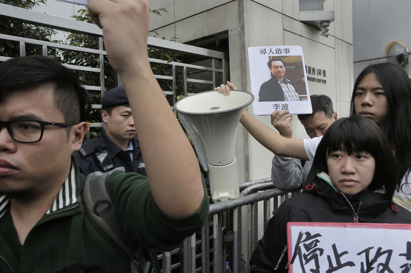 File - A protester holds a photo of missing bookseller Lee Bo during a protest outside the Liaison of the Central People's Government in Hong Kong on Sunday, January 3, 2016. Photo: AP
