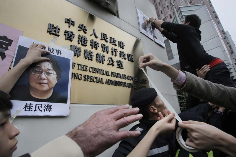 Protesters try to stick photos of missing booksellers during a protest outside the Liaison of the Central People's Government in Hong Kong, on Sunday, January 3, 2016. Photo: AP