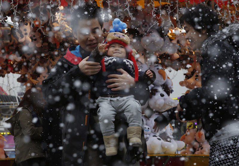 A family enjoys the artificial snow made of foam at a carnival in Hong Kong, on Tuesday, January 26, 2016. Photo: AP