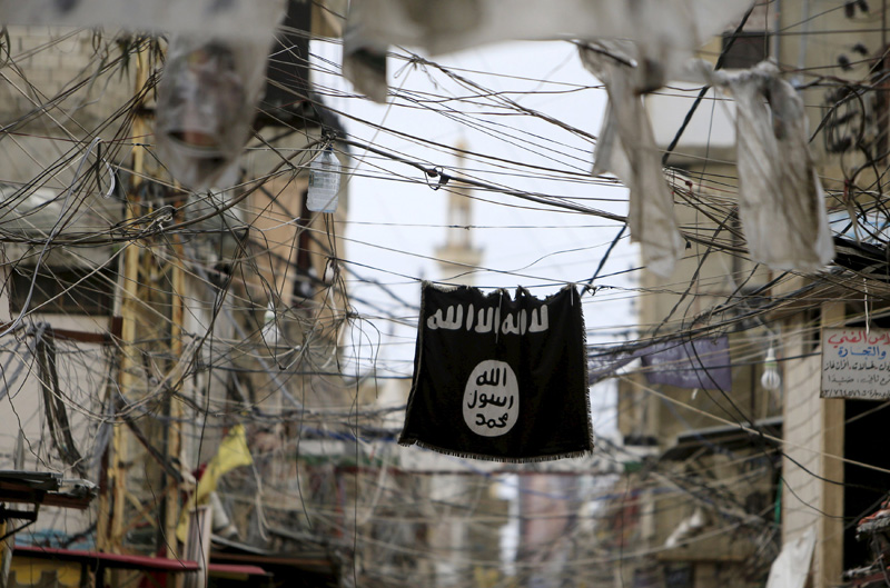 An Islamic State flag hangs amid electric wires over a street in Ain al-Hilweh Palestinian refugee camp, near the port-city of Sidon, southern Lebanon January 19, 2016. Photo: Reuters