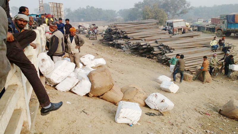 Goods brought from Raxaul are unloaded at the Miteri Pul right in front of protesters. Photo: Ram Sarraf