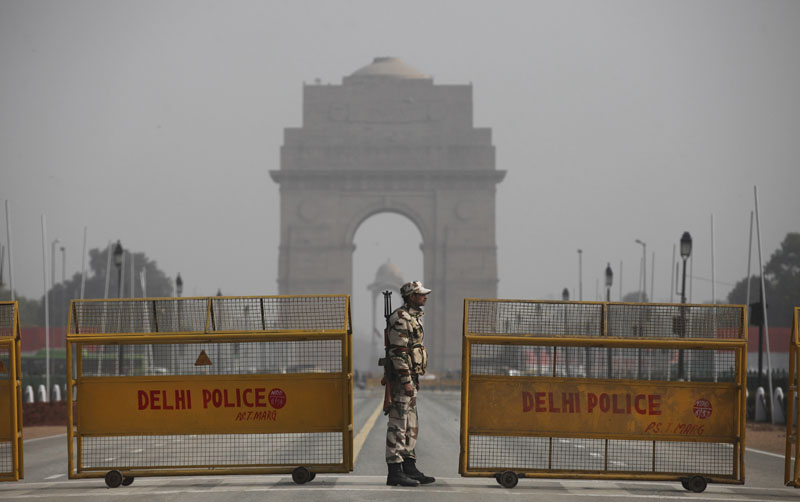 An Indian paramilitary soldier stands guard near a police barricade in front of India Gate, the landmark war memorial on Rajpath, the ceremonial boulevard for Republic Day parade in New Delhi, India, on Thursday, January 21, 2016. Photo: AP
