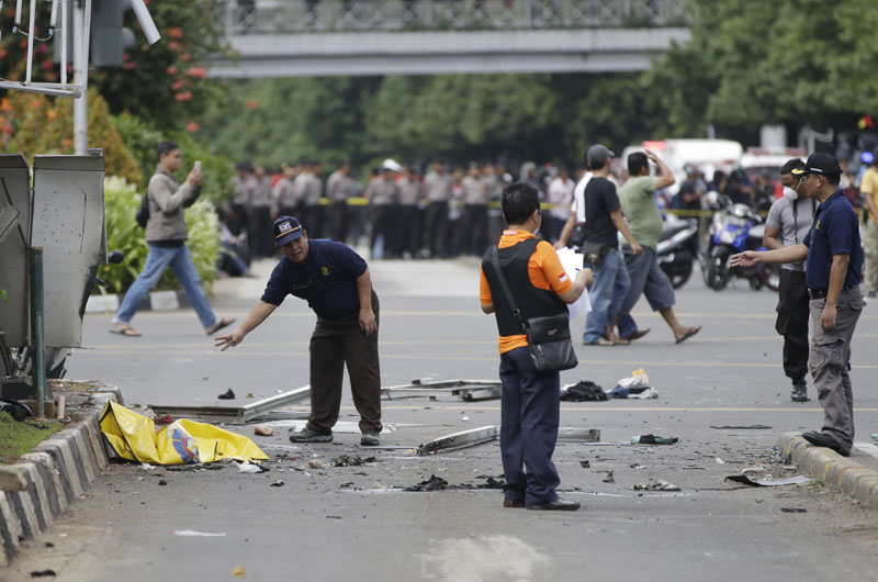 Police officers examine debris at the site where an explosion went off in Jakarta, Indonesia on Thursday, January 14, 2016. Photo: AP