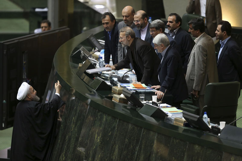 FILE - Iranian President Hassan Rouhani (left) presents a draft of the country's new budget and sixth development plan to the parliament speaker Ali Larijani in an open session of parliament, in Tehran, Iran on Sunday, January 17, 2016. Photo: AP