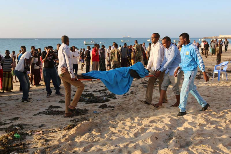 Relatives carry the body of their kin killed in an attack at beachside restaurant Beach View Cafe, on Lido beach in Somalia's capital Mogadishu, on January 22, 2016. Photo: Reuters