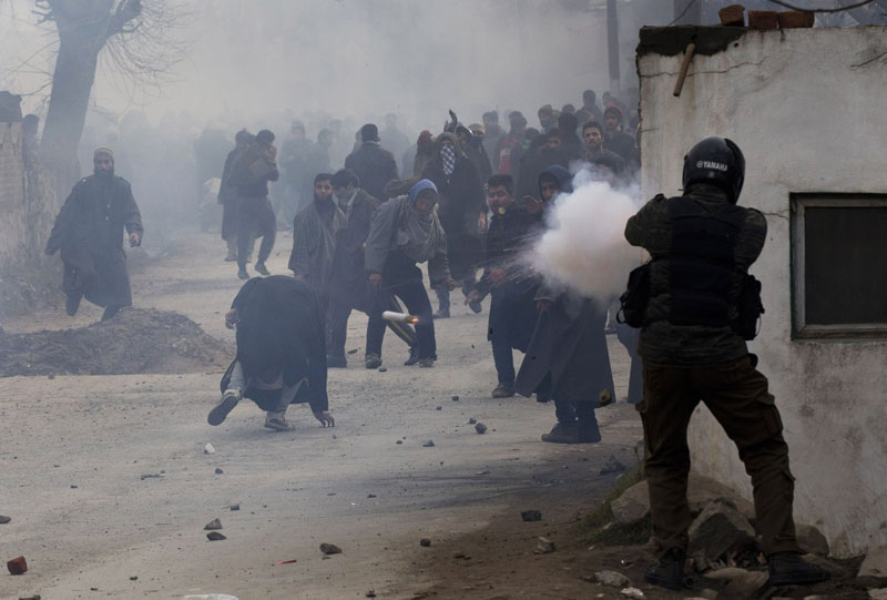 An Indian police officer fires a teargas shell as a Kashmiri Muslim (centre) ducks to avoid it during the funeral procession for Sajad Ahmed Bhat, a top rebel commander, on the outskirts of Srinagar, in Indian-controlled Kashmir, on Tuesday, January 12, 2016. Photo: AP