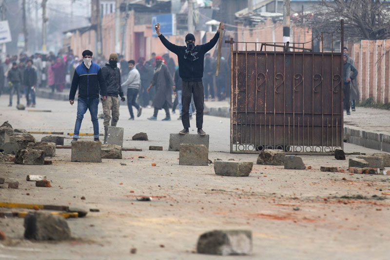 A Kashmiri Muslim protester (centre) holds a rock and a stick as he stands on a concrete block near a road blockade set up for Indian police during a protest in Srinagar, Indian-controlled Kashmir, on Thursday, January 14, 2016. Photo: AP