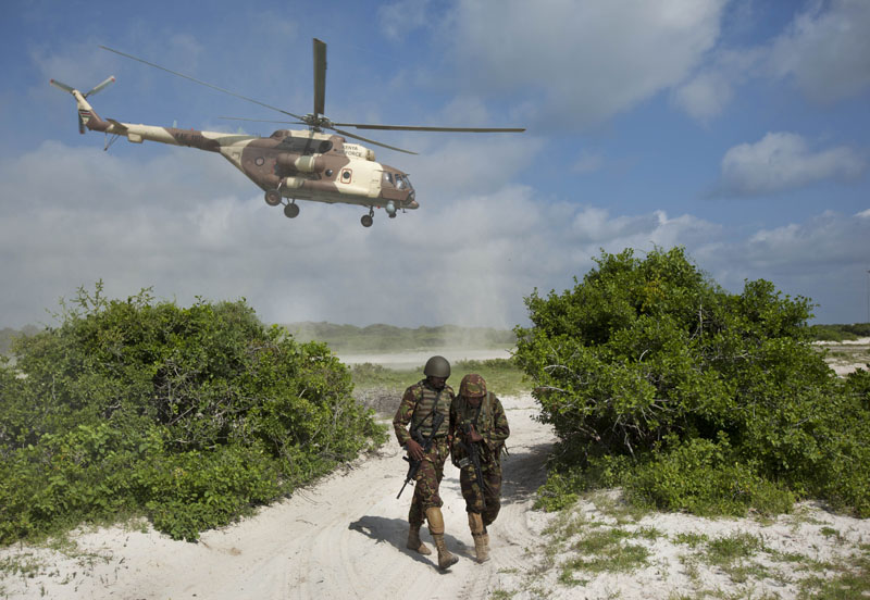 FILE -  Two Kenyan army soldiers shield themselves from the downdraft of a Kenyan air force helicopter as it flies away from their base near the seaside town of Bur Garbo, in Somalia on Wednesday, December14, 2011. Photo: AP