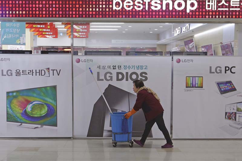 A worker passes by banners advertising LG Electronics products at a shopping mall in Seoul, South Korea, on Tuesday, January 26, 2016. Photo: AP