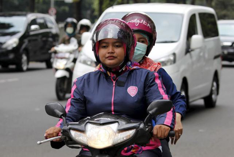 A Ladyjek driver (left) carries a customer as they ride a motorcycle at a street in Jakarta, January 11, 2016. Picture taken January 11, 2016. Photo: Reuters