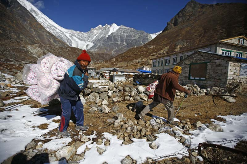 Earthquake survivors head home carrying blankets they received from the Association of Nepalis in Minnesota (ANMN) in Langtang village on Monday, January 25, 2016. Photo: Skanda Gautam/ THT