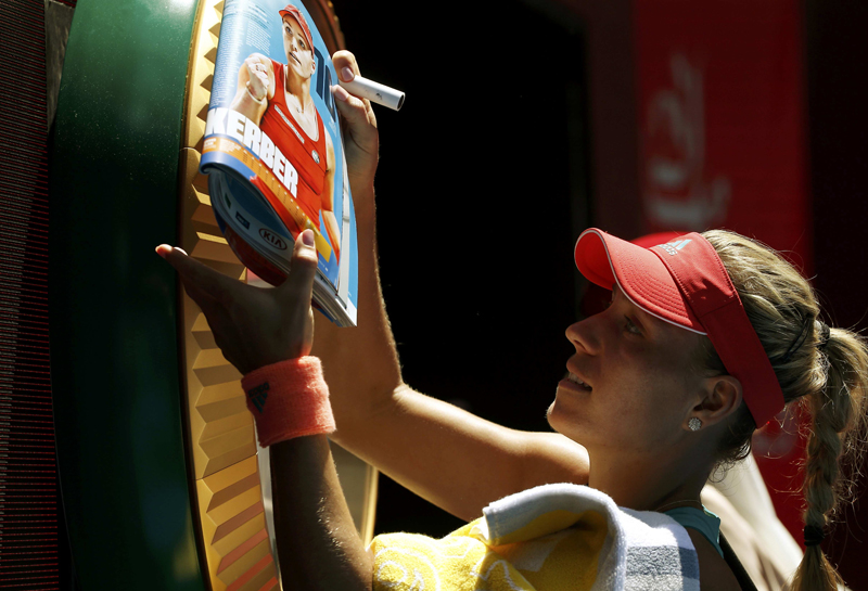 Germany's Angelique Kerber signs autographs after winning her fourth round match against compatriot Annika Beck at the Australian Open tennis tournament at Melbourne Park, Australia, January 25, 2016. Photo: Reuters
