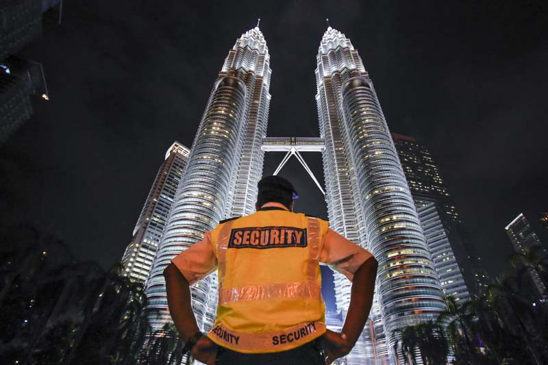 A security guard stands guard in front of Malaysia's iconic building, Petronas Twin Towers in Kuala Lumpur, Malaysia, Thursday, January 14, 2016. Photo: AP