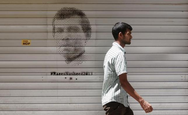 A Maldivian man walks past an image of Mohamed Nasheed in Male, November 7, 2013. REUTERS/ Stringer/Files