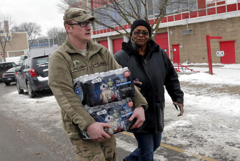 Michigan National Guard Staff Sergeant William Phillips (L) assists a Flint resident with bottled water at a fire station in Flint, Michigan January 13, 2016. Photo: Reuters