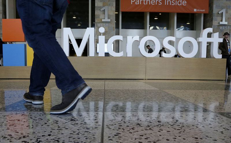 FILE - A man walks past a Microsoft sign set up for the Microsoft BUILD conference at Moscone Center in San Francisco on April 28, 2015. Photo: AP