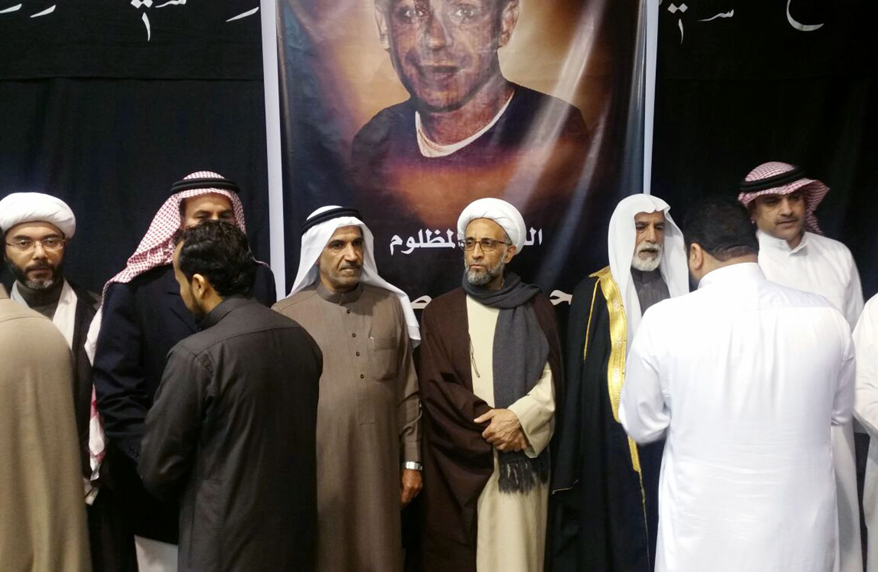 Sheikh Hassan al-Saffar, a top Shiite cleric from Qatif, center, stands with family members of Shiite Sheikh Nimr al-Nimr and other Shiite notables, as they receive condolences on the second day of mourning for him at a mosque in the village of al-Awamiya, eastern Saudi Arabia on Tuesday, January 5, 2016. Photo: AP