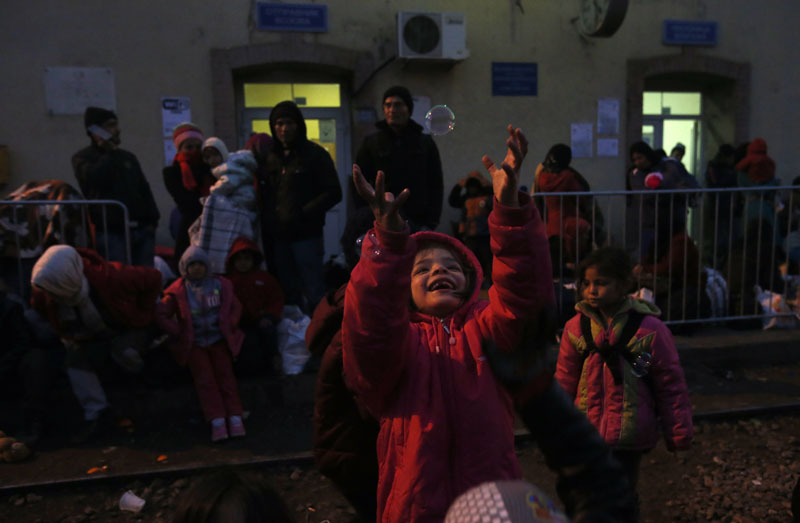 Migrant children play with soap bubbles as they wait at the railway station in the southern Serbian town of Presevo, on Wednesday, December 23, 2015. Photo: AP
