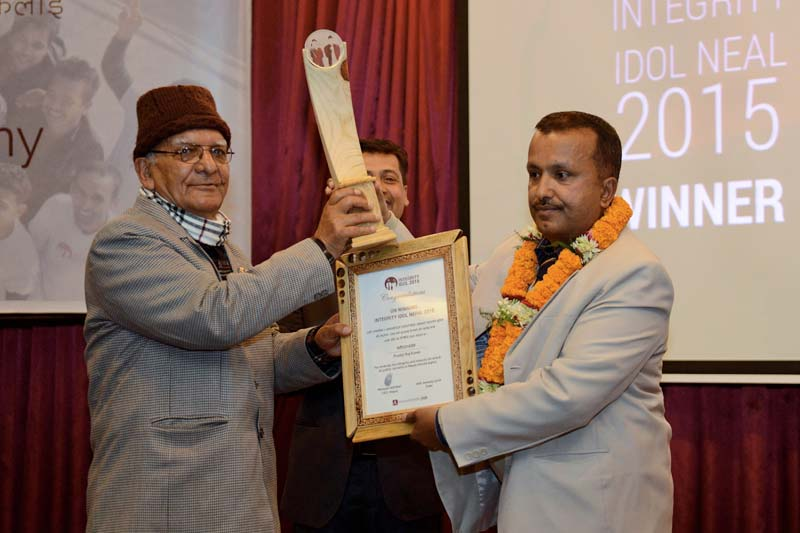 Nepali Co-operatives and Poverty Alleviation Minister, Chitra Bahadur (left) hands the Integrity Idol trophy to civil servant and district administrator, Pradip Raj Kandel (right) during an awards ceremony in Kathmandu on January 10, 2016.  Photo: AFP