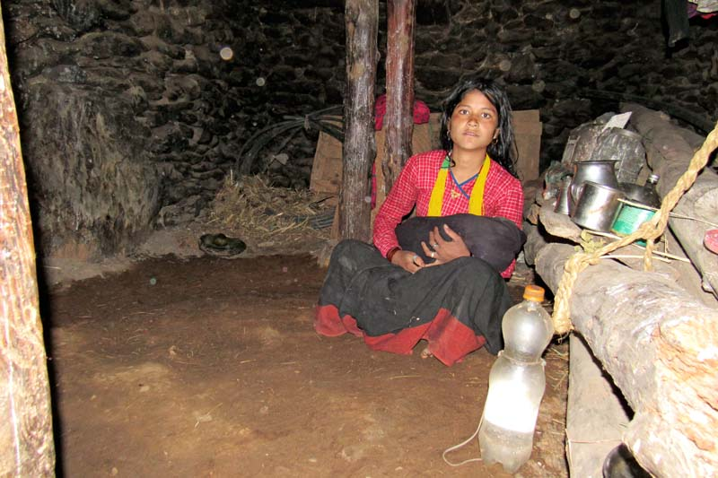 A new mother holds her baby inside a cowshed, where they stay for a month after the baby is born, in Maila VDC of Humla district, on Tuesday, January 26, 2016. Photo: Prakash Singh/ THT