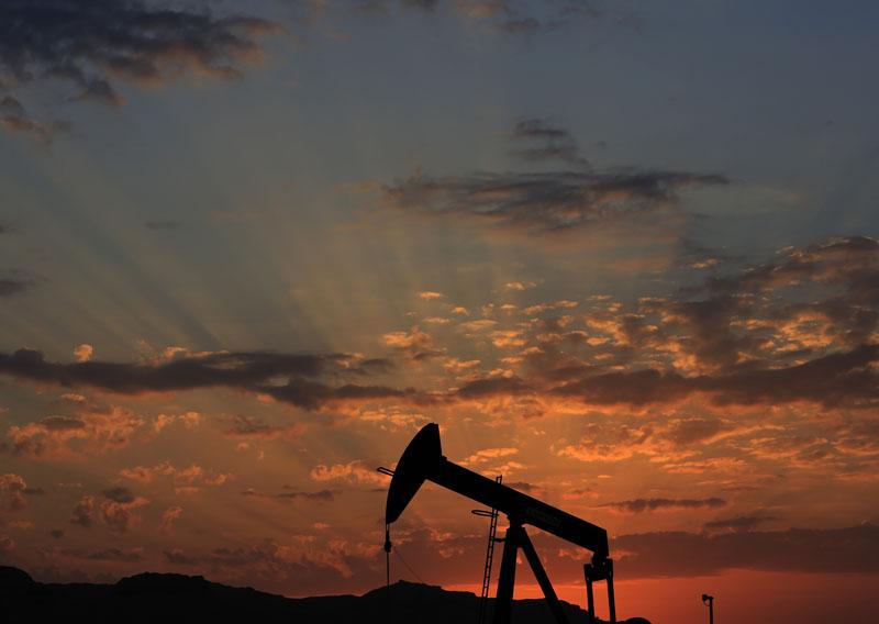 FILE - The sun sets behind an oil pump in the desert oil fields of Sakhir, Bahrain on December 13, 2015. Photo: AP