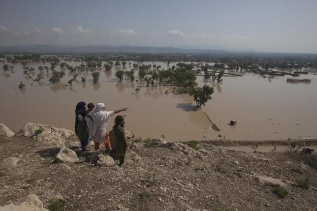 In this image taken on July 31, 2010, a family points towards partially submerged houses while taking refuge on a hilltop overlooking the flooded town of Nowshera, northwest Pakistan. REUTERS/Adrees Latif/Files
