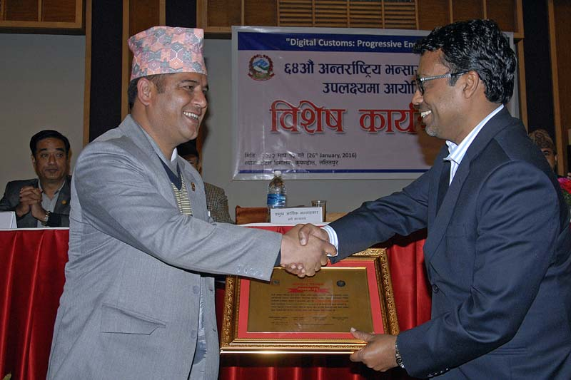 Pashupati Murarka (right) receiving a letter of felicitation from Damodar Bhandari, State Minister for Finance, during a programme organised to mark the 64th International Customs Day, in Kathmandu, on Tuesday. Photo: THT