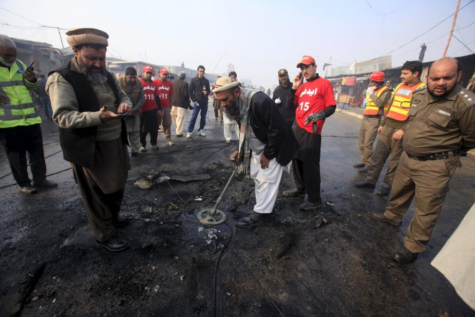 Investigators look for evidence after a suicide bomber blew himself up close to a police checkpoint in Peshawar, Pakistan January 19, 2016.    REUTERS/Fayaz Aziz