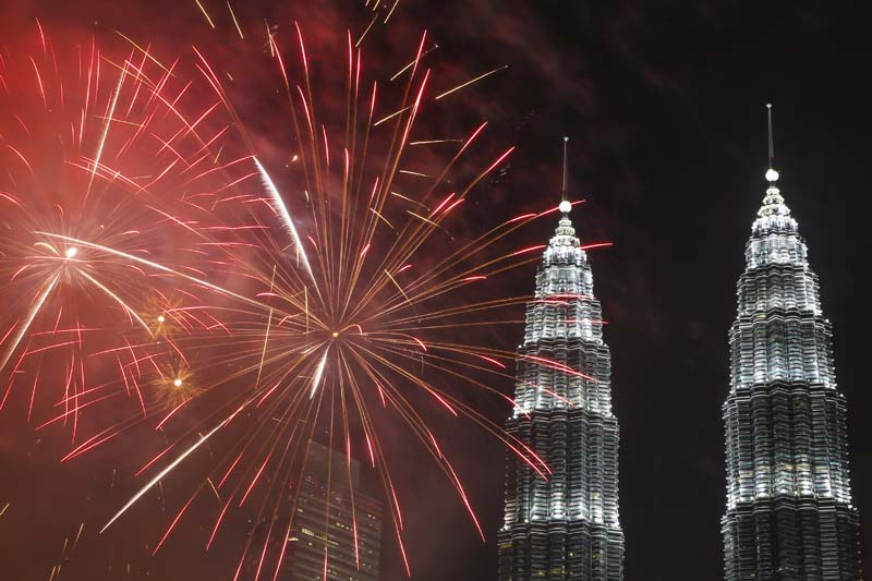 Fireworks explode in front of Malaysia's landmark building, Petronas Twin Towers, during the New Year's Eve celebration in Kuala Lumpur, Malaysia, Friday, January 1, 2016. Photo: AP