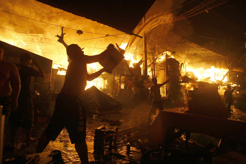A man throws a bucket of water to help firemen battle a fire that occurred as Filipinos welcome the New Year at a poor Manila district of Tondo Friday, January 1, 2016 in the Philippines. Photo: AP