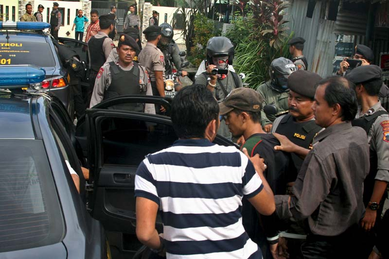 Police officers escorts a man (centre with a cap) who was arrested during a raid in the Langgen village in Tegal, Indonesia Central Java, on January 15, 2016. Photo: Antara Foto via Reuters