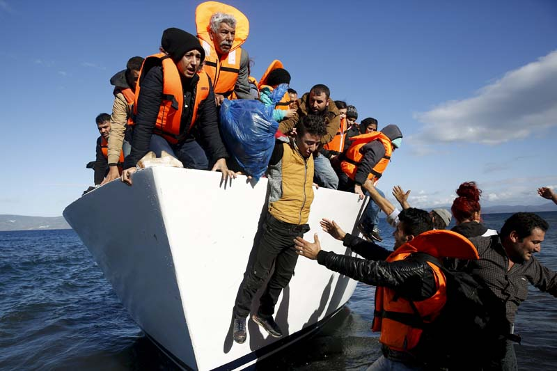 Refugees and migrants jump off a boat as they arrive on the Greek island of Lesbos, in this November 26, 2015 file photo. Photo: Reuters/ File