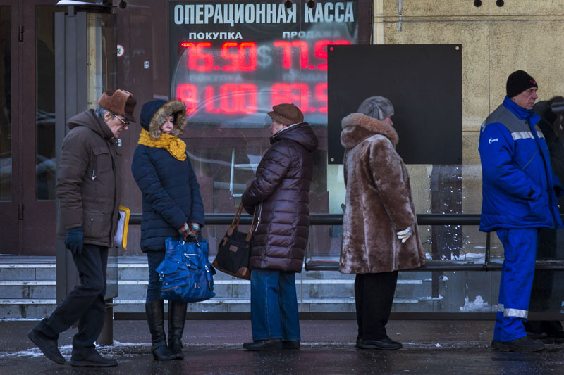 People stand at a bus stop in front of an exchange office sign showing the currency exchange rates of the Russian ruble, US dollar, and euro in Moscow, Russia, on Monday, January 11, 2016. Photo: AP