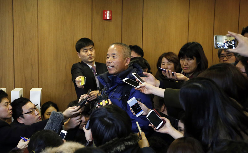 Hwang Sang-gi (centre) father of former Samsung semiconductor speaks to the media after reaching a partial agreement in Seoul, South Korea, on Tuesday, January 12, 2016, after factory worker Hwang Yu-mi who died from leukemia in 2007. Photo: AP