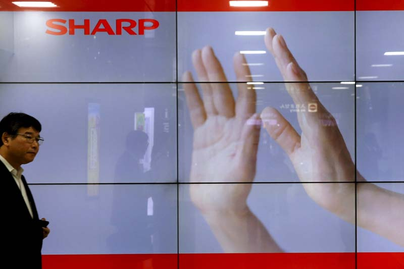 A man walks past display showing a logo of Sharp Corp in Tokyo, Japan, on October 30, 2015. Photo: Reuters/ File