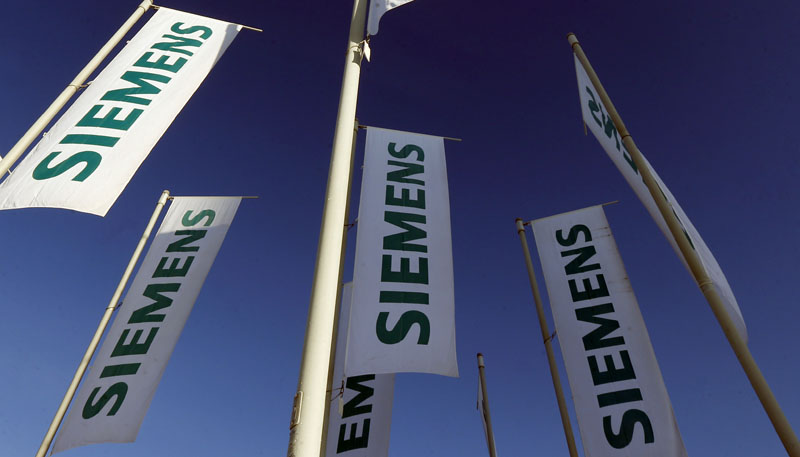 FILE - flags of German engineering conglomerate Siemens AG  fly during a  annual shareholder meeting in Munich, southern Germany, on January 23, 2013. Photo: AP