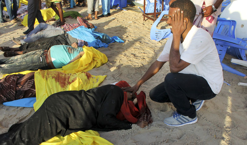 A Somali man cries after identifying the dead body of his sister on the beach following an overnight attack on a beachfront restaurant in Mogadishu, Somalia, on Friday, January 22, 2016. Photo: AP