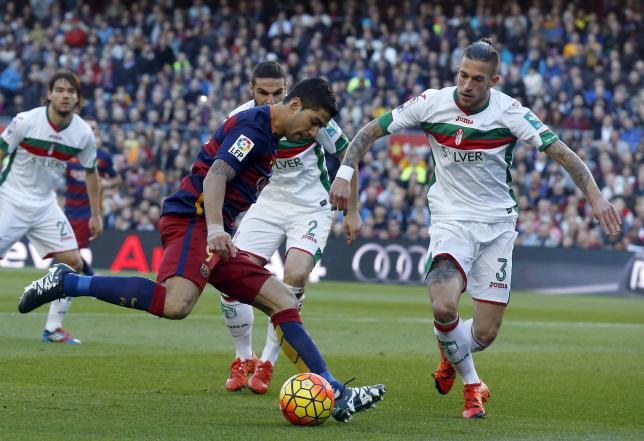 Barcelona's Luis Suarez (L) against Granada's Cristiano Biraghi. REUTERS/Albert Gea