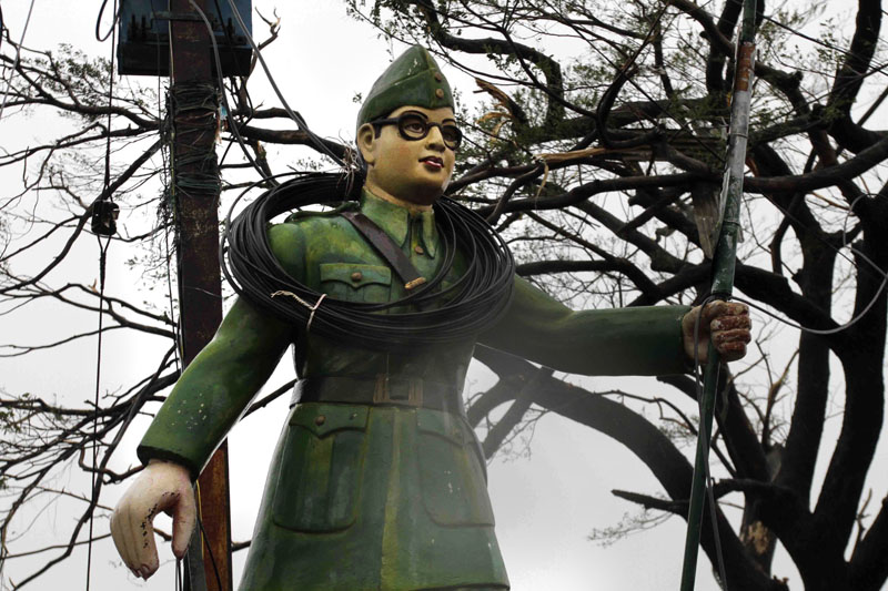 FILE-  Electric wires are entangled around a statue of Indian freedom fighter Subhash Chandra Bose at road crossing during a cyclone in Berhampur, India, on October 13, 2013.  Photo: AP