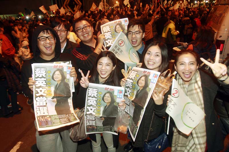 Supporters of Democratic Progressive Party (DPP), presidential candidate Tsai Ing-wen show extra editions to cheer at the campaign headquarters as early polling numbers arrive in her favor, on Saturday, January 16, 2016, in Taipei, Taiwan. Photo: AP