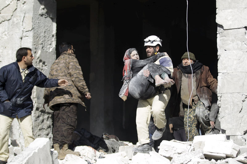 Civil defence member carrying an injured woman from  a site hit by what activists said were airstrikes carried out by the Russian air force, in the rebel-controlled area of Maaret al-Numan town, in Idlib province, Syria, on Saturday. Photo: Reuters