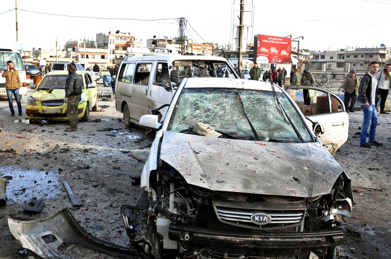 Syrian citizens gather at the scene where twin bombs exploded at a government-run security checkpoint, at the neighborhood of Zahraa, in Homs province, Syria, on Tuesday, January 26, 2016. Photo: SANA via AP